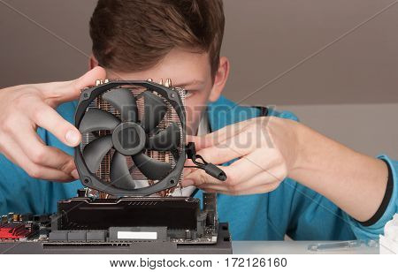 Young Man Installing Cpu Cooler Fan On Gaming Motherboard