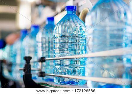 Plastic water bottles on conveyor and water bottling machine industry