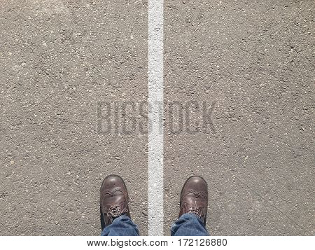 standing on the asphalt concrete floor and white line between his legs like he is on both side and cannot make the decision which way to go - left or right.