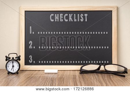 CHECKLIST word on chalkboard with chalk and glasses.