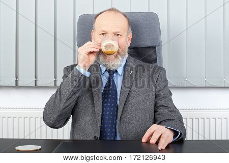 Picture of a thoughtful manager having a coffee break at the office