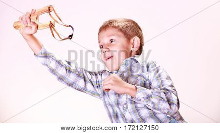 Nature and free time prankster little boy. Child have fun with wooden sling shot and fruit aim mandarine.
