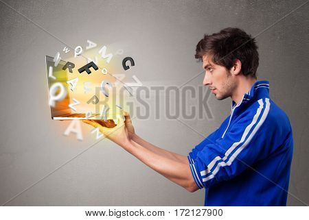Attractive casual young man hoding notebook with colorful letters