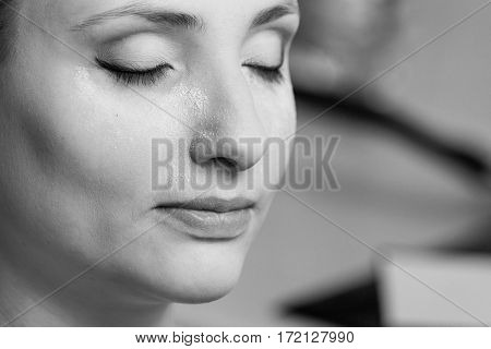 Visage cosmetics concept. Woman with full make up closeup powder dust on cheeks baking method black and white