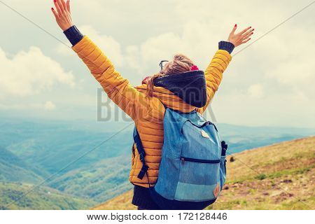 Girl enjoying on a mountain top with arms wide open.