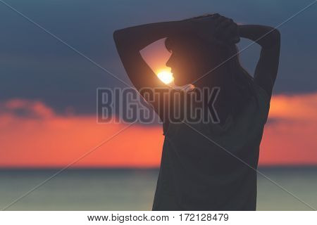 Silhouette of a woman at sunset / sunrise time with ocean background.