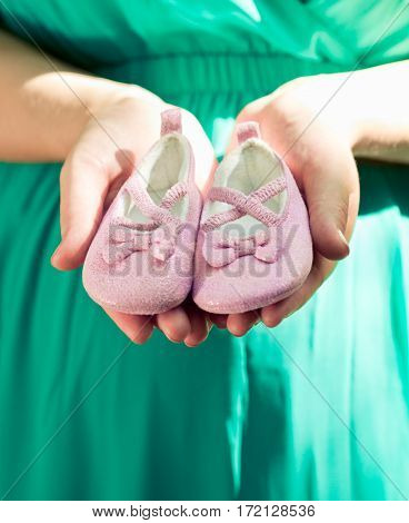 Pregnant Woman In Green Dress Belly Holding Pink Baby Booties, Expecting Girl.