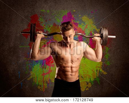 A muscular young bodybuilder lifting weight and showing his hot body with muscles in front of an urban painted wall concept