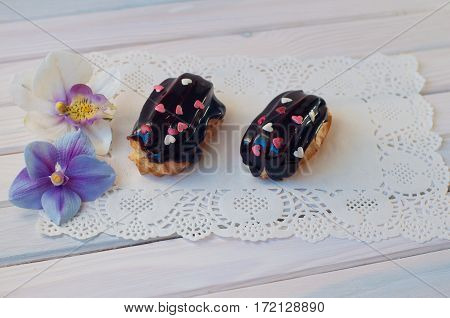 Two eclairs with dark chocolate cover and small confectionery heart sprinkles lay on white lace serviette on wooden table near orchid flowers