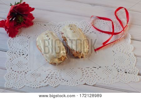 Two eclairs covered by white chocolate with small silver balls and red poppy flower ribbon lay on white lace serviette on wooden table
