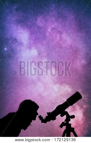 Girl looking at the stars through a telescope. Stars are de-focused.