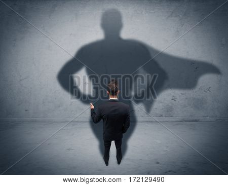 A confident young elegant salesman with briefcase facing a wall, looking at his  shadow concept