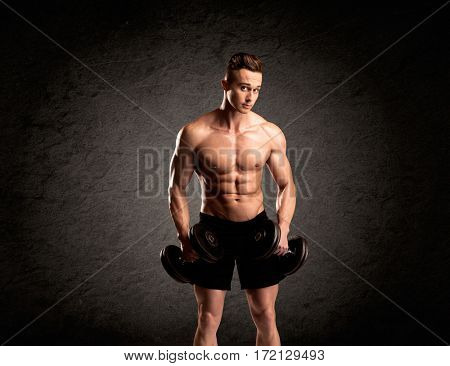 A handsome fitness guy lifting weight and showing his strong muscles in front of a black urban concrete wall concept