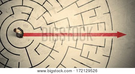 Business person standing in the middle of a circular maze with red arrow