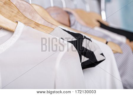 black and white womens clothes on wooden hangers on a rack in a fashion store. closet business woman