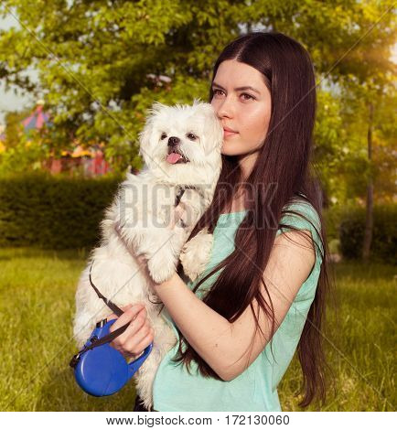 Beautiful girl with a young dog enjoying a beautiful day in the outdoors