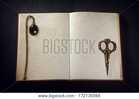 Vintage Open Book On A Black Background. Vintage Pendant On The Pages Of The Old Book.
