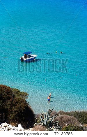 ISTRO, CRETE - SEPTEMBER 18, 2016 - Elevated view of tourists and a boat in the sea Istro Crete Greece Europe, September 18, 2016.