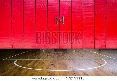 Close up wooden floor basketball court with red door