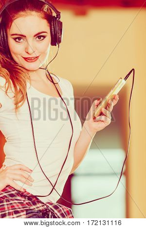 Hobby music technology and free time. Young girl use phone listen music with headphones choose tracks.