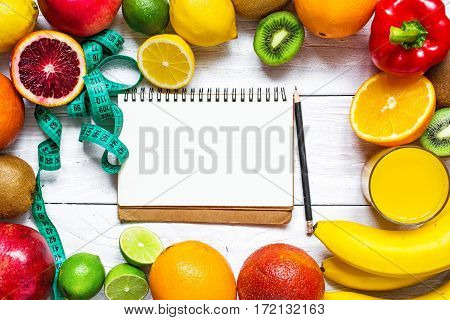Fitness concept with fruits, vegetables, orange juice, centimeter and text book on white wooden background with copy space. Top view