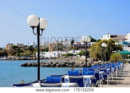 MAKRIGIALOS, CRETE - SEPTEMBER 18, 2016 - View of the beach and town with cafe tables in the foreground Makrigialos Crete Greece Europe, September 18, 2016.