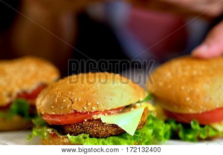 Hamburger fast food with ham on wooden board . Group of hamburger. Human hand holding cheeseburger.
