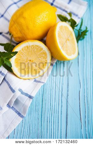 Fresh Half And Whole Lemons On Blue Rustic Boards.