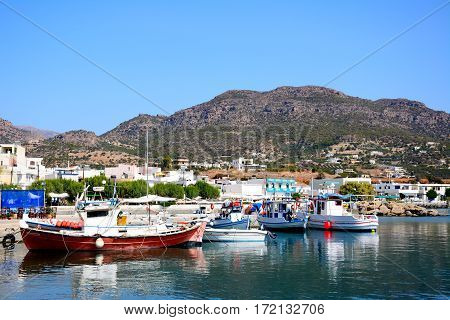 MAKRIGIALOS, CRETE - SEPTEMBER 18, 2016 - Traditional fishing boats in the harbour with views towards the town and mountains Makrigialos Crete Greece Europe, September 18, 2016.