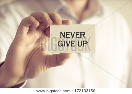 Businessman Holding Never Give Up Text Card
