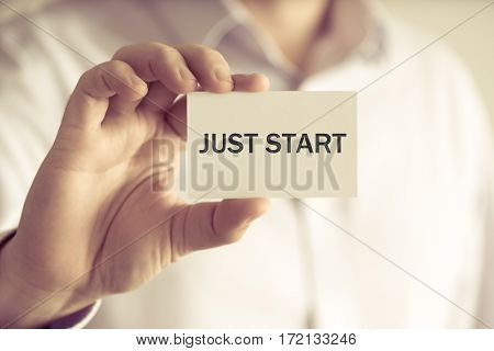 Businessman Holding Card With Text Just Start