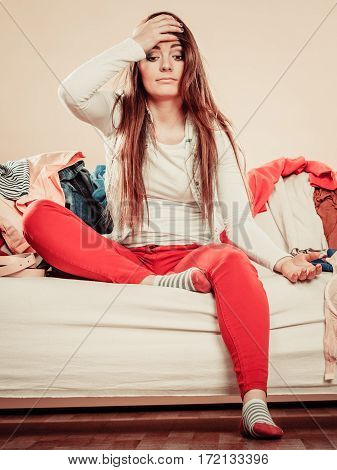 Confused Woman Sit On Sofa Full Of Clothes.