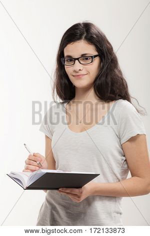 Young secretary with glasses and agenda, wearing t-shirt, portrait in studio