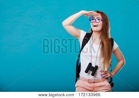 Summer holidays and tourism concept. Attractive woman long hair with backpack holding binocular on blue