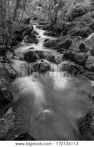 A black and white slow exposure river scene with large boulders in Vietnam.