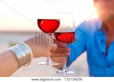 Close-up Of Two Human's Hand With Wineglasses Red Wine During Sunset.