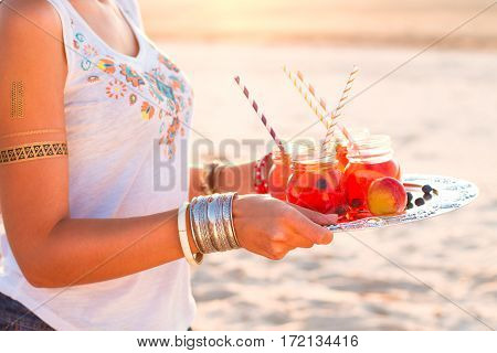Woman Holds A Dish With A Drinks At Sunset. Picnic Theme