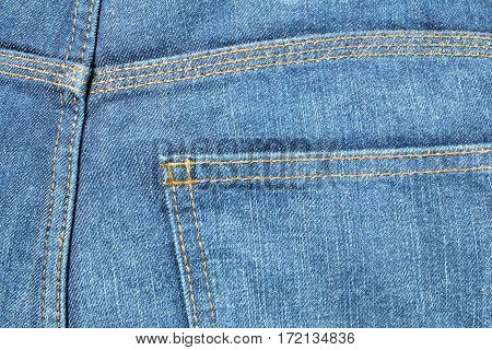 Blue denim stonewashed jeans back pocket with orange stitching
