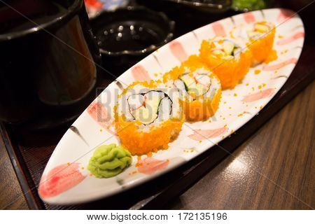 sushi set sashimi and sushi rolls served on wooden plate