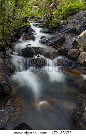 A slow exposure river scene with large boulders and lush vegetation in Vietnam.
