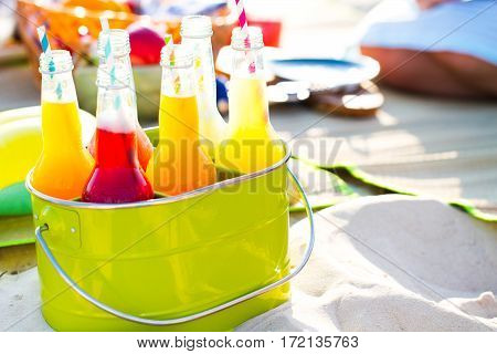 Bottles Of Lemonade, Standing In A Colorful Green Bucket On The Beach In The Summer Sun.