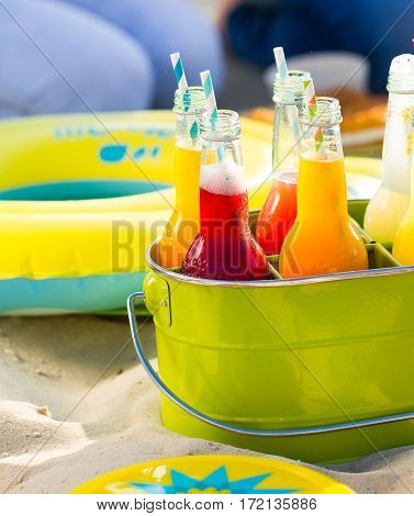 Bottles Of Lemonade , Standing In A Colorful Green Bucket On The Beach In The Summer Sun.
