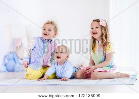 Group of three kids playing in a white bedroom. Children play at home. Preschooler girl toddler boy and baby in nursery. Happy little brothers and sister bonding having fun together. Siblings love.