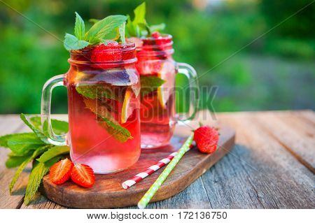 Red Lemonade With Strawberries And Mint On An Old Wooden Table In A Summer Garden