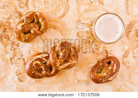 Several salty cooked pretzel and lager beer seen from above over the greaseproof paper