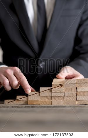 Vertical close-up of businessman building career ladder stairs or growing graph concept of wooden domino bricks with upcoming arrow.