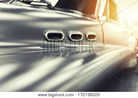 Closeup on a grey vintage car in the sunlight