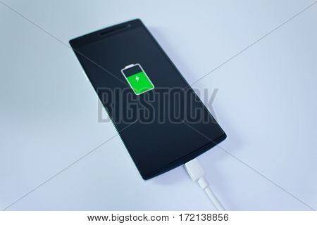Mobile smart phone is charging with graphic on it screen