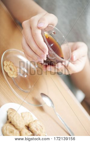 Human hands holding cup of tea with cookies