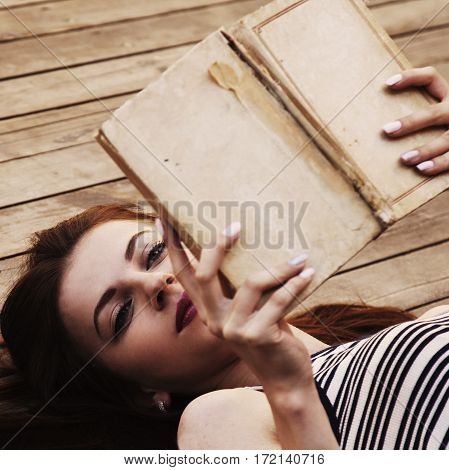 Beautiful young woman reading a book. (relax romance poetry rest)